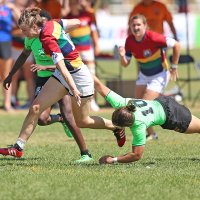 Anna Symonds being tackled by an opposing team in a rugby match.