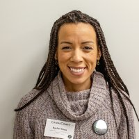 Dr. Rachel Knox, an African-American woman, stands smiling in front of a white background. She is wearing a grey cowl-neck sweater.