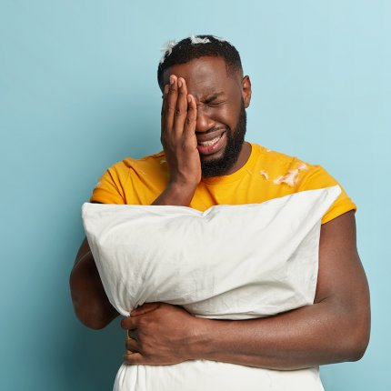 An African American man stands hugging a pillow with one hand to his face. He is wearing a bright yellow shirt and standing in front of a blue background. There are feathers on his shoulder and head. He looks frustrated and tired.