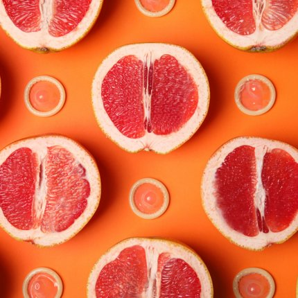A flat lay of grapefruits cut in half interspersed with condoms on a bright orange background.