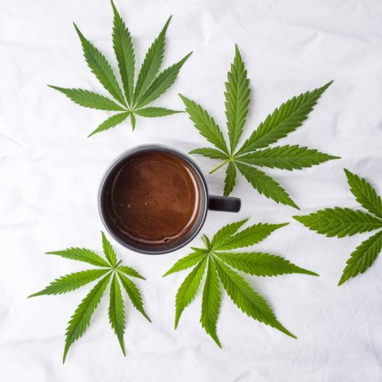 Marijuana leaves and a cup of coffee on white