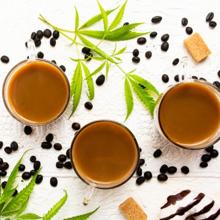 Cups of coffee with marijuana and roasted beans on a table