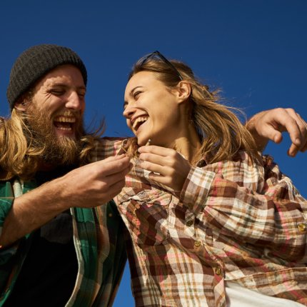 A young couple, one male presenting and one female presenting, laugh and hug while sharing a joint in front of an open blue sky.