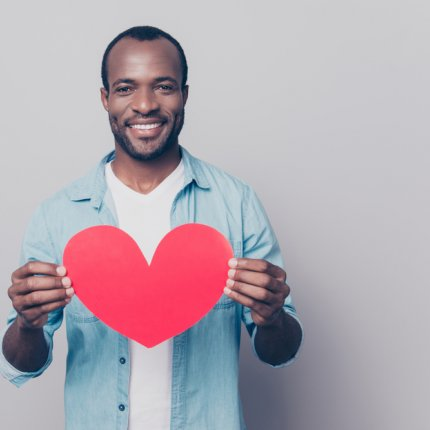 Portrait of tender gentle romantic sweet lovely open-hearted african man showing big red heart in hands isolated on gray background
