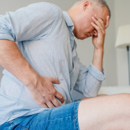 ULcerative colitis. Frustrated man hugging his belly and keeping eyes closed. Disturbed male having pain in stomach.