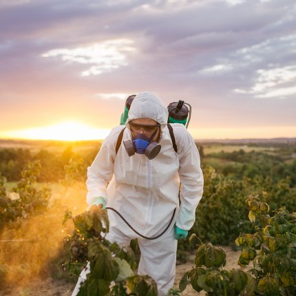 farm worker spraying pesticides