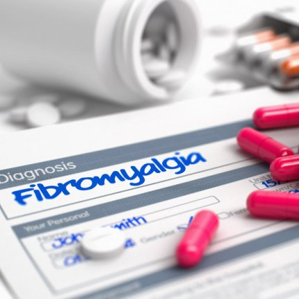 """""""Fibromyalgia"""" handwritten on a diagnosis pad, surrounded by heaps of white and pink pills, on a white background."""