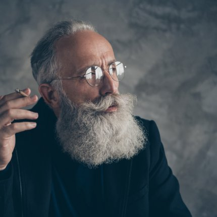 Close-up portrait of an attractive Caucasian elderly gentleman. He has a long white beard, and a neatly groomed mustache, as well as round glasses on. He is smoking a joint in front of a grey concrete wall.