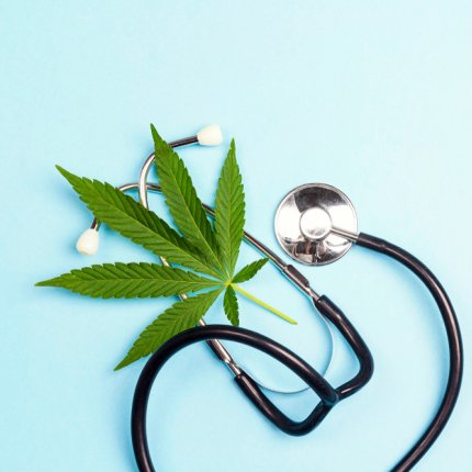 A stethescope and cannabis leaf on an aqua background.