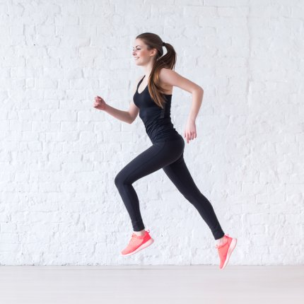 Side view of active sporty young running woman. She is wearing pink gym shoes and black leggings and a black tank top.