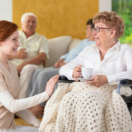 A young red-haried woman holds the hand of an elderly woman in a wheelchair. The young woman is wearing tan scrubs and kneeling next to the wheelchair. They are both smiling and looking at each other.