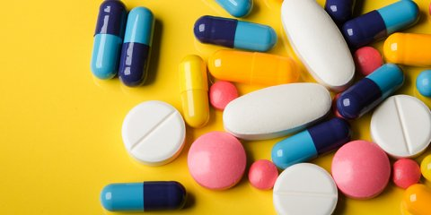 colorful pills against yellow background