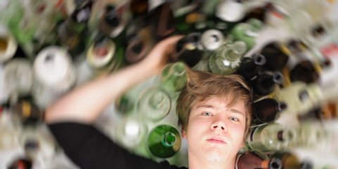 Illustration of a young man surrounded by alcohol bottles