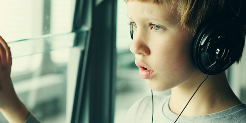 Boy with headphones looking out window