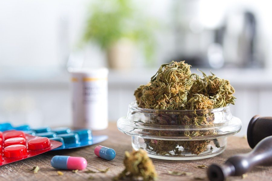 Cannabis buds in small container, pills, and pipe on a table
