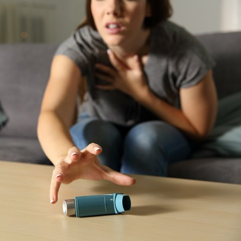 woman grabbing for inhaler during asthma attack