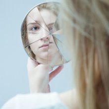 woman looking in cracked mirror