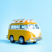 A toy model of a yellow VW bus sits on a light blue background.