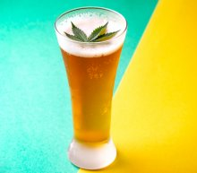 A cold glass of beer with cannabis leaf floated on top of the head, sits in front of an aqua and yellow background. The colors are split on an angle, and the beer sits on the split.