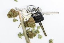 A joint, loose flower, and a set of Subaru car keys on a white background.