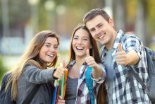 Three happy students looking at you with thumbs up in an university campus.