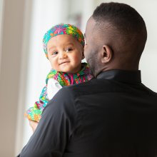 African American man holding adorable baby girl