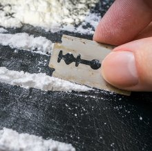 Lines of cocaine and razor in hand