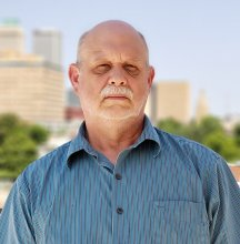 Will Foster, a middle-aged white man with a receding hairline, stands in front of an Oklahoma skyline. He is wearing a short-sleeve blue button-up shirt.