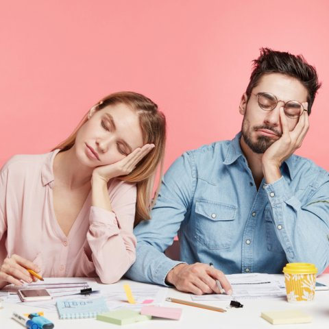 A white woman and white man sit behind a desk covered in office supplies. They are both leaning their heads into their left hands, with their eyes close. The woman is wearing a pinkblouse, and the man is wearing a blue jean shirt. They are in forn of a pink background.