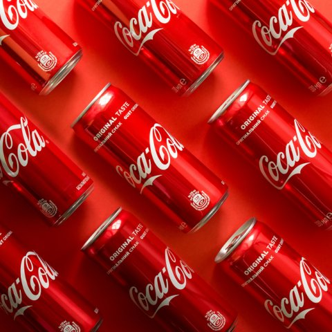 A pattern of red coca cola cans in parallel lines on a forty-five degree angle on a background of the same color.