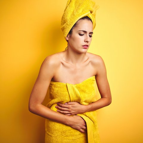 A young woman wearing a yellow towel wrapped around her body and a yellow towel twisted on her head holds her stomach. She looks nauseous.