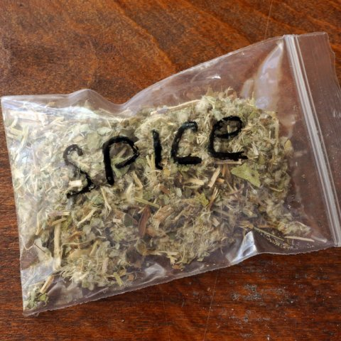 A clear plastic baggie labeled 'spice' in black sharpie filled with dried herbs sits on a faux-wood background.
