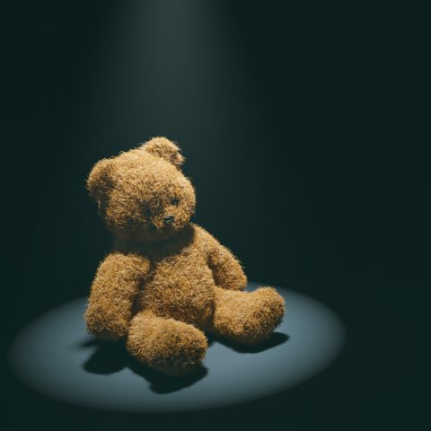 A worn teddy bear sits in a spotlight on a dark background.