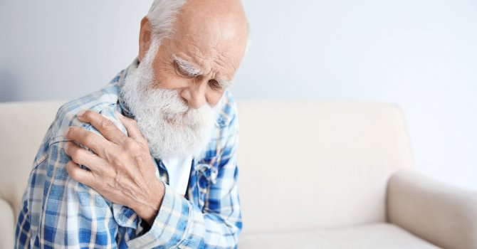 Senior man in a blue plaid shirt holds his painful shoulder on cream colored couch.