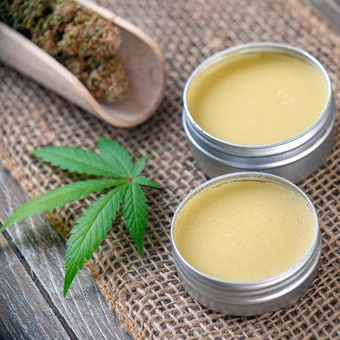 Photograph of two tins of topical cannabis balm restin on top of a burlap-covered table. There is a wooden scoop filled with cannabis flower, and a fresh cannabis leaf next to the two tins.
