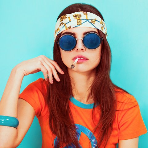 A young white woman wearing and orange t-shirt, sunglasses, and a floral-printed headband smokes a joint in front of an aqua background.