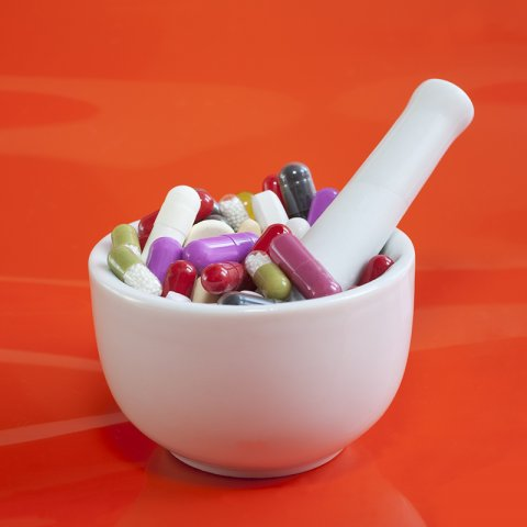 mortar and pestle with pills and orange background