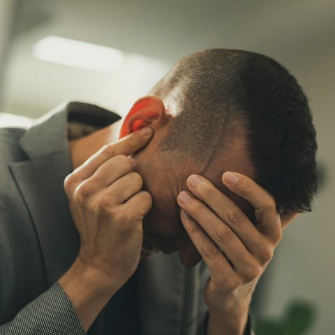 Distraught man holding head
