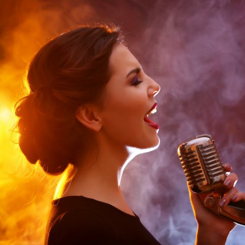woman singing in colorful smoke