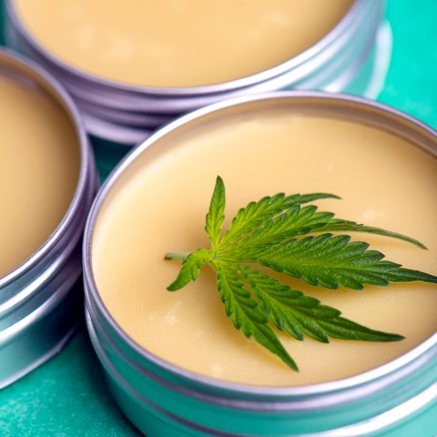 Photograph of three tins of slave. The focus of the image is a tin with a cannabis leaf laid on top of the salve.