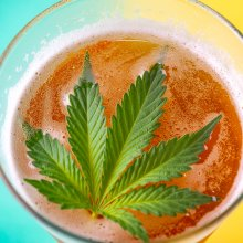 Overhead photograph of a glass of beer on an aqua and yellow background with a cannabis leaf floating on the surface of the beer.