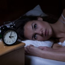 woman looking at clock in the middle of the night