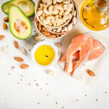 A cut avocado, bowl of olive oil, salmon fillet, bowls of cashews, pistachios, and almonds sit on a white marble background.