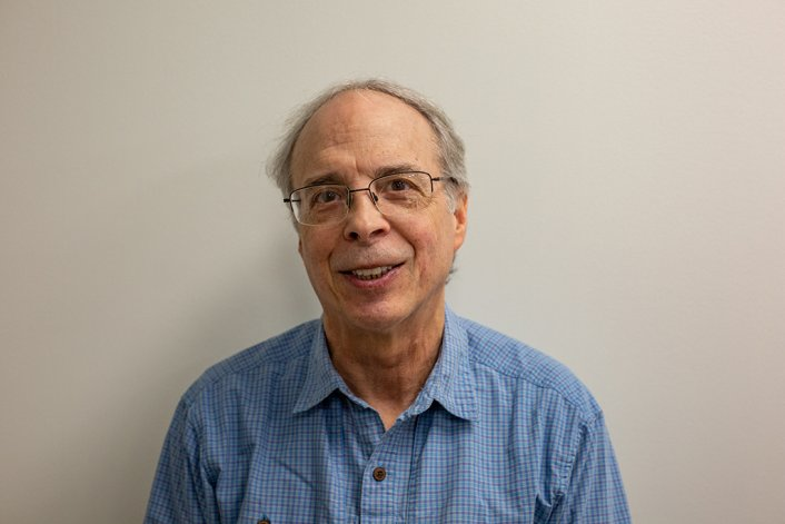 Dr. Ethan Russo, a middle-aged white man with glasses and thinning grey hair, stands against a white background. He is wearing a casual blue button-up shirt.